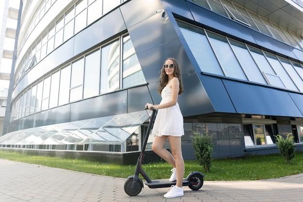 Uma garota que anda de scooter elétrica na cidade