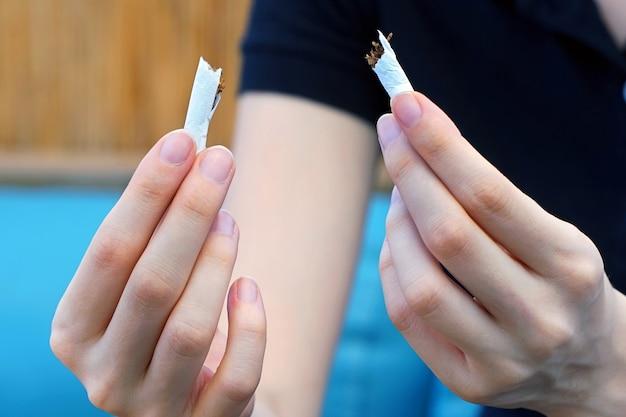 Uma garota quebra um cigarro. parar de fumar.