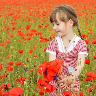 Uma garota recolhe flores de papoula