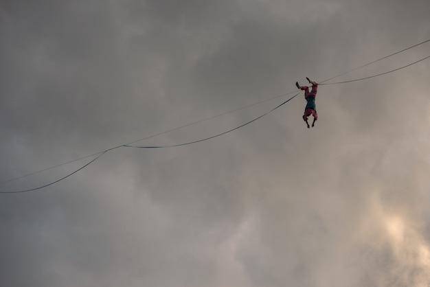 Uma garota ropewalker pendurada de cabeça para baixo no highline contra o fundo de um céu dramático