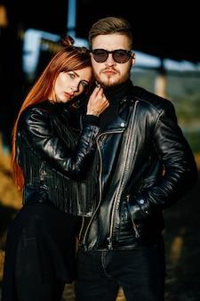 Uma garota ruiva e magra em roupas pretas toca a barba do namorado