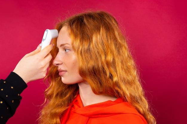 Uma garota ruiva é medida com um termômetro sem contato em sua testa. conceito de vírus e pandemia.
