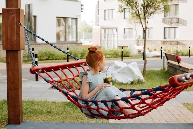 Uma garota ruiva está sentada em uma rede com um copo de limonada gelada.