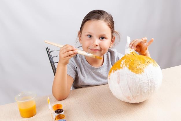 Uma garota se senta a uma mesa e pinta uma abóbora de papel machê, faça você mesmo para o halloween.