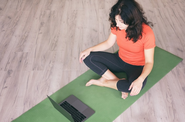 Uma garota se senta em casa em um tapete esportivo, olha para o computador e se exercita