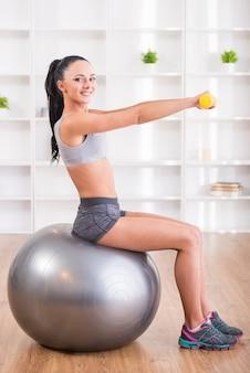 Uma garota se senta em uma bola de fitness e realiza um exercício.