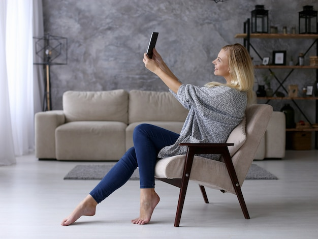 Uma garota se senta em uma cadeira e tira fotos em um tablet. trabalhe confortavelmente em casa remotamente via vídeo. copyspace.