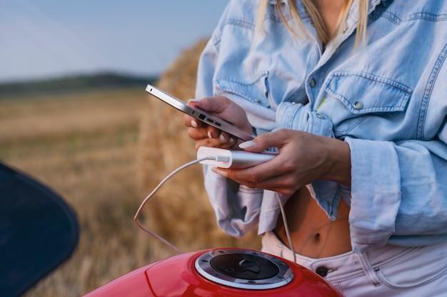 Uma garota se senta em uma motocicleta e segura uma maquete de um smartphone com uma tela branca. power bank carrega seu telefone contra o pano de fundo da natureza.