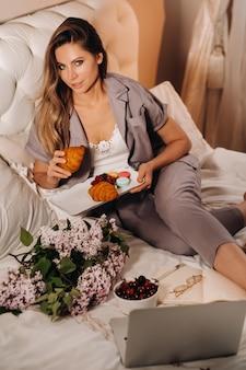 Uma garota se senta na cama à noite assistindo um laptop e comendo morangos, uma garota na cama come doces antes de ir para a cama.