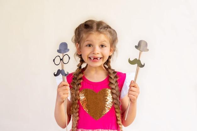 Uma garota segura um bigode chique e um chapéu para o dia dos pais.