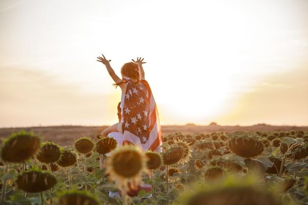 Uma garota segura uma bandeira americana ao pôr do sol.