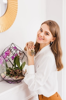 Uma garota segura uma florariumov, forma de vidro com suculentas, pedras e areia, decorada com fitas de natal. presentes de natal para casa e escritório.