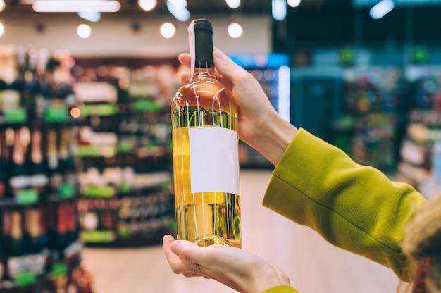 Uma garota segura uma garrafa de vinho na loja.