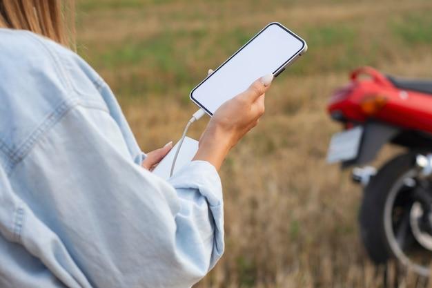 Uma garota segura uma maquete de um smartphone com uma tela branca nas mãos. power bank carrega o telefone tendo como pano de fundo a natureza e uma motocicleta.
