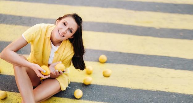 Uma garota segurando limões nas mãos, vestida com uma camisa amarela, shorts e sentada em uma faixa de pedestres amarela