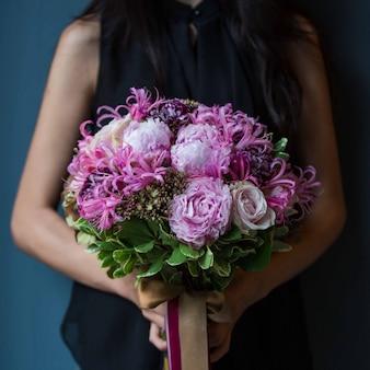 Uma garota segurando um buquê de tipos de flores roxas com as duas mãos