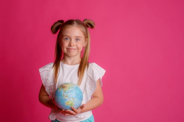 Uma garota segurando um globo no estúdio em uma rosa