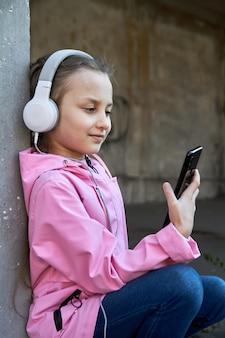 Uma garota segurando um smartphone na mão e ouvindo música em fones de ouvido