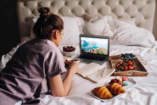 Uma garota senta na cama à noite, com um smartphone na mão e come morangos, uma garota na cama come doces antes de ir para a cama ..
