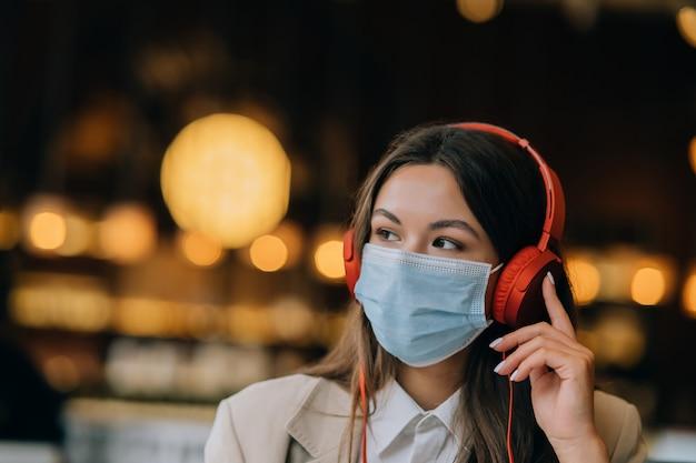Uma garota sentada em um café com fones de ouvido e máscara facial durante o surto de coronavírus