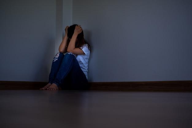 Uma garota sentada em um canto escuro da sala sozinha está tendo problemas.