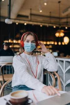 Uma garota sentada em uma cafeteria com surto de coronavírus em fones de ouvido