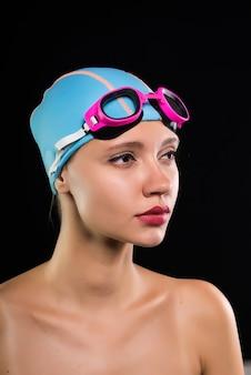 Uma garota séria de touca e óculos está se preparando para nadar, piscina