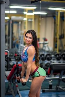Uma garota sexy bonita e atlética treina e faz fitness no ginásio. fitness, musculação.