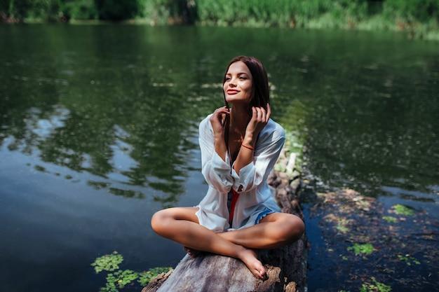 Uma garota sexy em uma camisa branca senta-se em um tronco na posição de lótus perto do rio. o conceito de recreação ao ar livre.