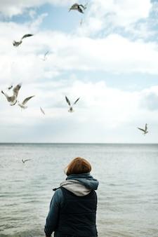 Uma garota solitária de camiseta regata e um suéter rosa com capuz alimenta gaivotas à beira-mar.