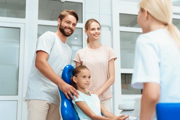 Uma garota sorri e fala com o médico. ao lado de seus pais