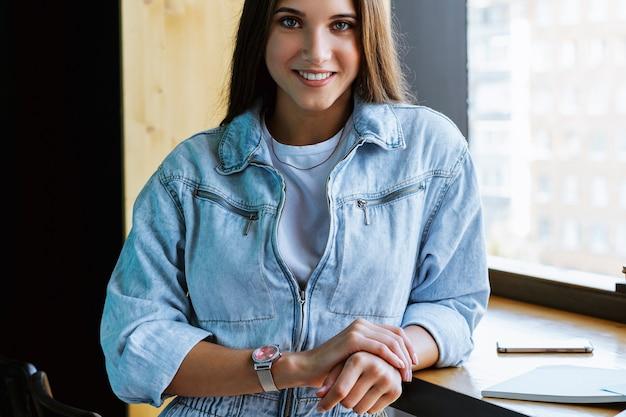 Uma garota sorridente em roupas jeans fica na frente da câmera perto da janela e se inclina sobre a mesa.