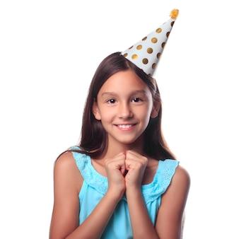 Uma garota sorridente feliz em um chapéu festivo, esperando por uma celebração de férias