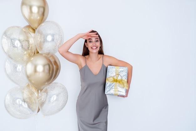 Uma garota sorridente segurando uma caixa de presentes perto de balões de ar olha para a distância, veio a celebração