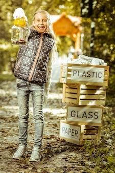 Uma garota sorridente separando o lixo na floresta em um dia bom