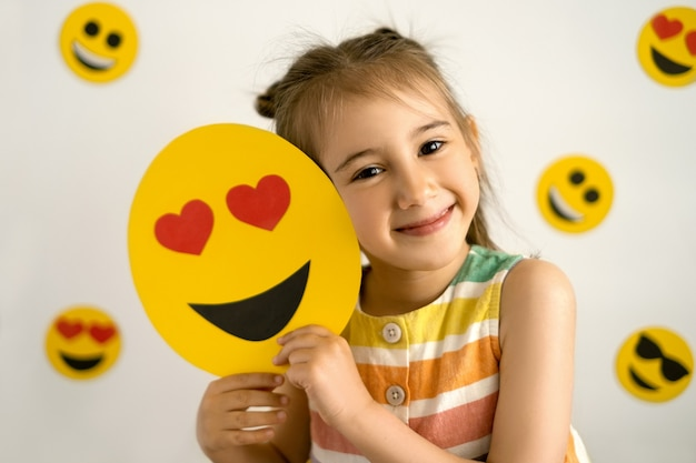 Uma garota sorrindo com todos os dentes segurando um emoji de amor nas mãos