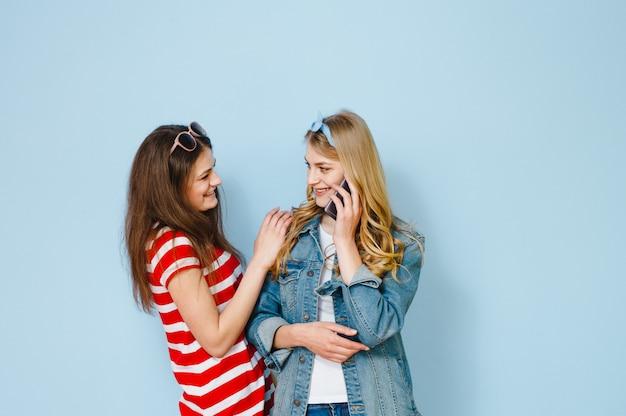 Uma garota sussurra algo no ouvido da namorada, olhando para o celular