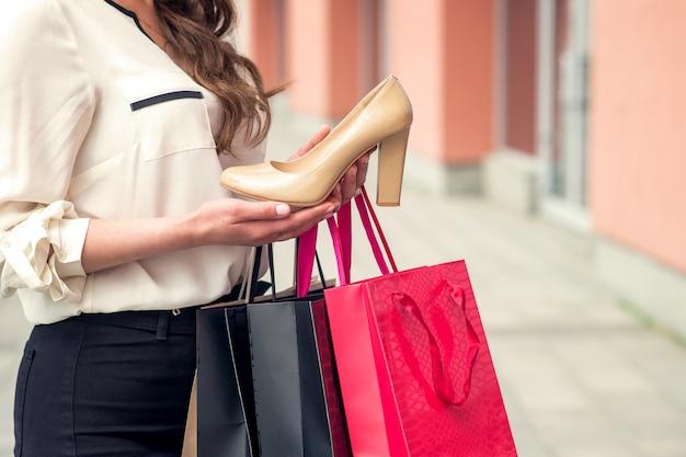 Uma garota tem um excelente sapato branco e sacos de papel. copie o espaço