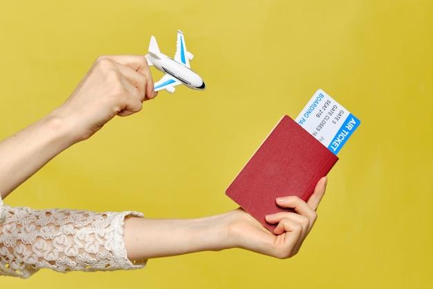 Uma garota tem um passaporte com passagens aéreas ee um avião abstrato.
