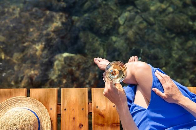 Uma garota tem uma taça de vinho na mão enquanto está sentado em um píer de madeira perto do mar adriático. chapéu de palha, férias, viagens. vista de cima.