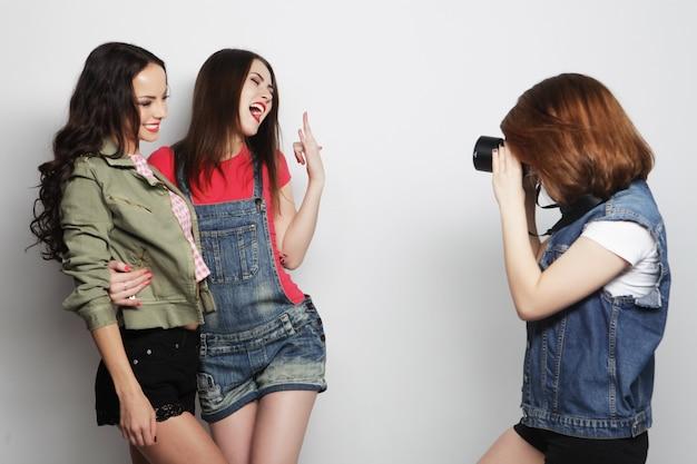 Uma garota tira foto de seus amigos. conceito de amizade e diversão. melhores amigos, aproveitando o momento com a câmera moderna.
