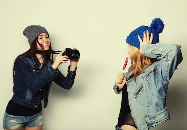 Uma garota tira foto de sua amiga em frente a um fundo branco