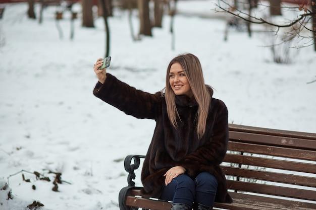 Uma garota tira fotos suas no seu telefone