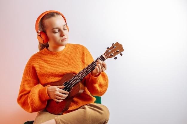 Uma garota toca ukulele