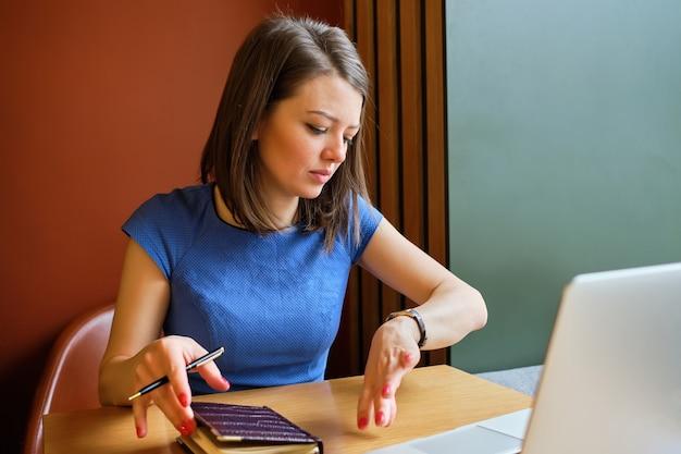 Uma garota trabalha em um laptop e olha para o relógio. conceito de defasagem de reunião.