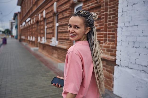 Uma garota travessa com uma camiseta rosa e dreadlocks desce a rua rindo e olhando strai ...