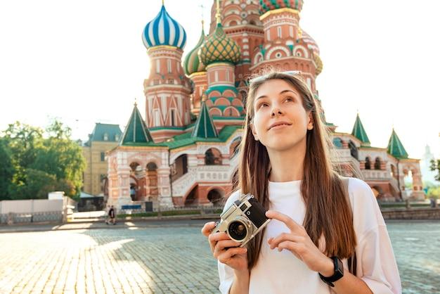 Uma garota turista com uma câmera sorri em um dia ensolarado no contexto da catedral de são basílio