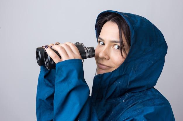 Uma garota turista com uma capa de chuva azul segura binóculos nas mãos e olha para longe, espiões.