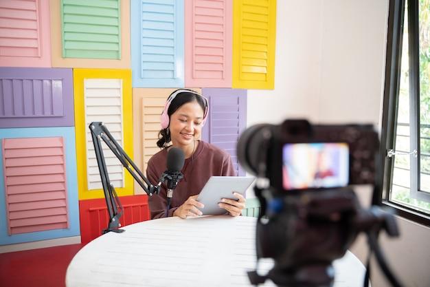 Uma garota usando fones de ouvido na frente de um microfone lendo em um tablet enquanto um podcast