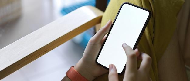 Uma garota usando smartphone enquanto está sentado na poltrona ao lado da varanda na sala de estar